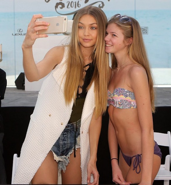 Model Gigi Hadid poses for a photo with a young fan in a bathing suit at the meet and greet.